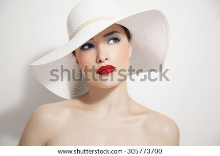 woman beauty portrait with red lips and summer white hat, studio - stock photo