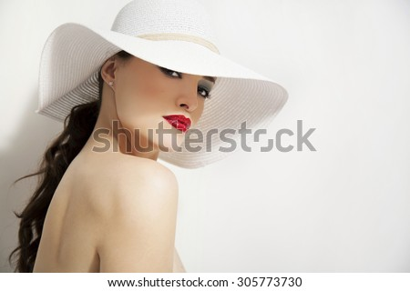 woman beauty portrait with red lips and summer white hat, studio