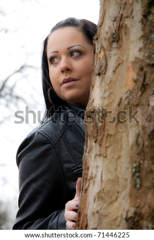 Woman behind a tree