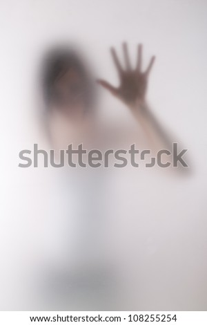 woman behind blurry glass - stock photo