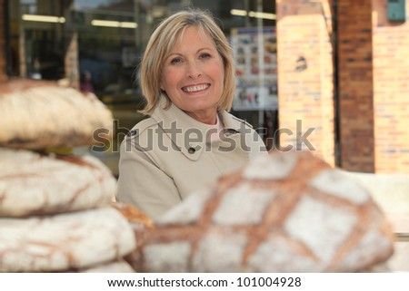 Woman behind loaves of bread - stock photo