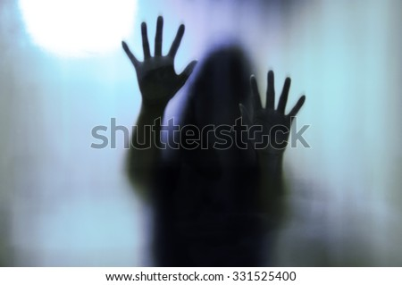 Woman behind the matte glass. Blurry hand and body figure - stock photo