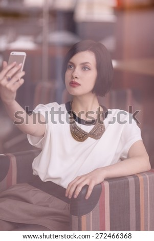 Woman behind the window taking selfie sitting in cafe - stock photo
