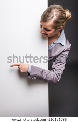 Woman behind white banner on dark gray background - stock photo