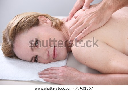 Woman being given a back massage and looking at us. - stock photo