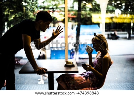 woman being ignored stopped by young handsome man looking at smartphone drink coffee on glass window in cafe background. Phone addiction concept. Human face expression emotions