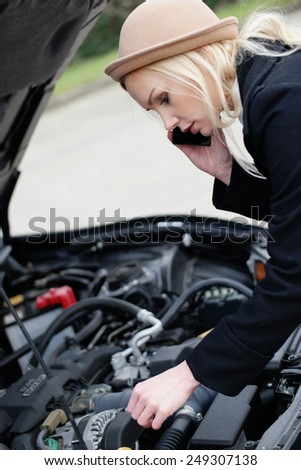 Woman being talked through roadside assistance on her broken down car on her mobile phone as she tinkers with the engine - stock photo