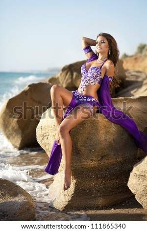 woman belly dancer on rock beach. dancing beautiful slim girl. sexy arabian turkish oriental professional artist in carnival blue costume and diamond jewelry outdoor. exotic bellydance star. Series - stock photo