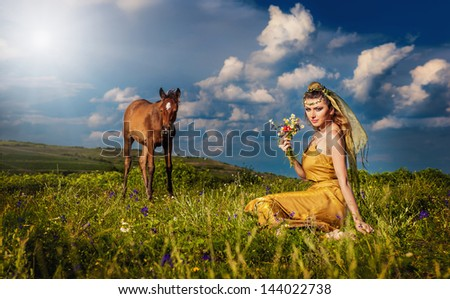 woman belly dancer relaxing on grass field against blue sky with white clouds. Sexy arabian turkish oriental professional artist in yellow costume and diamond jewelry outdoor. exotic belly-dance star. - stock photo