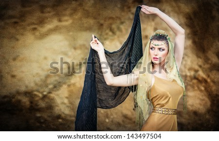 woman belly dancer with veil against rock beach. Dancing beautiful slim girl. Sexy arabian turkish oriental professional artist in yellow costume and diamond jewelry outdoor. exotic belly-dance star. - stock photo