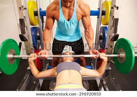 Woman bench pressing weights with assistance of trainer, front view - stock photo