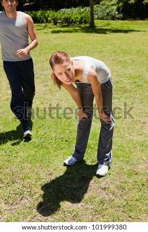 Woman bending over to recover while a man is jogging behind her on the grass