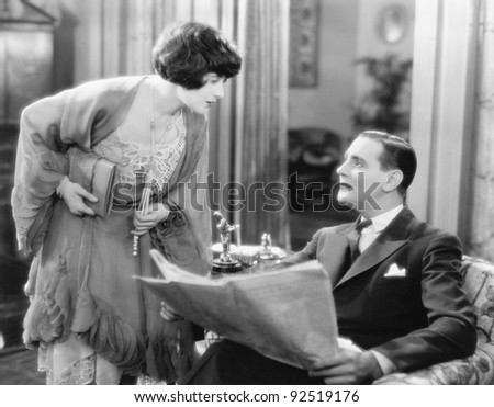 Woman bending over to talk to a man holding a newspaper - stock photo