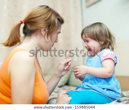 Woman berates crying baby at home interior. Focus on child only - stock photo