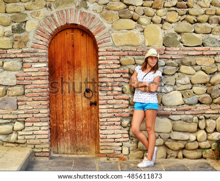 Woman beside stony wall of old church.