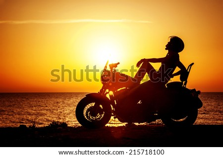 Woman biker enjoying sunset, female riding motorcycle, motorbike driver traveling the world, girl resting on the beach road, freedom lifestyle - stock photo