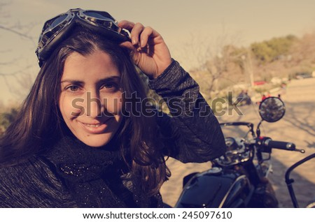 Woman biker looking at the view with glasses and vintage filter - stock photo