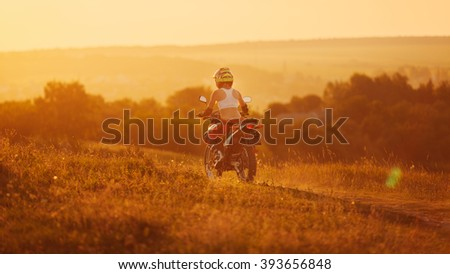 Woman biker rides in fields. Sporty woman biker at motobike. Countryside, country road.  sunset, female motorcycle rider, motorbike rider travel the world, girl resting, freedom lifestyle, back view - stock photo