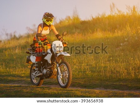 Woman biker rides in fields. Sporty woman biker at motobike. Countryside, country road.  sunset, female motorcycle rider, motorbike rider traveling the world, girl resting, freedom lifestyle - stock photo