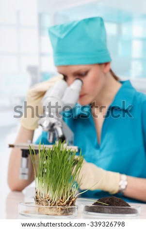 Woman biologist working with microscope - stock photo