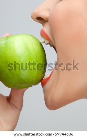 Woman biting apple. Side portrait of open mouthed woman about to bite green apple, studio background. - stock photo