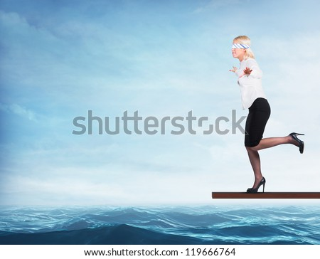 Woman blindfolded walking on a board over the sea - stock photo