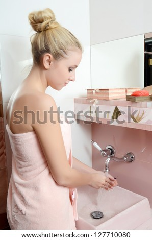 Woman blonde in pink towel washes hands