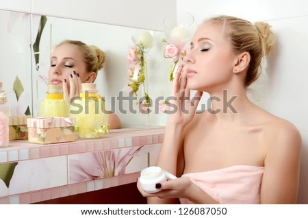 Woman blonde puts on face a cream