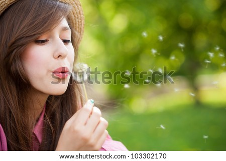 Woman blowing dandelion - stock photo