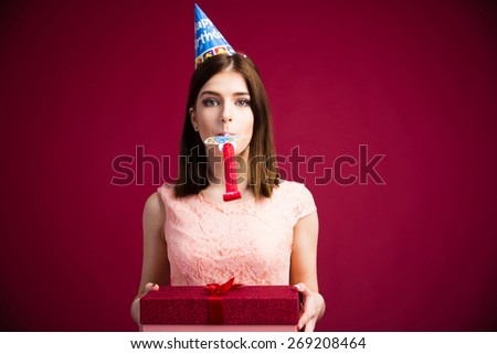 Woman blowing in whistle and holding gift box over pink background. Looking at camera. Wearing in dress - stock photo