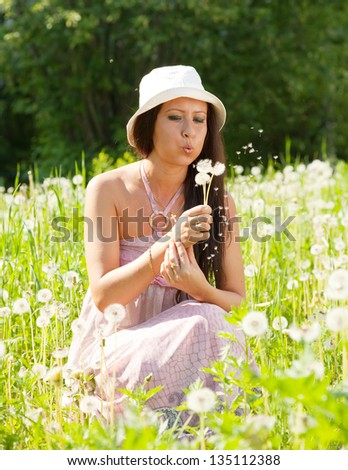 Woman blowing on dandelion in summer - stock photo
