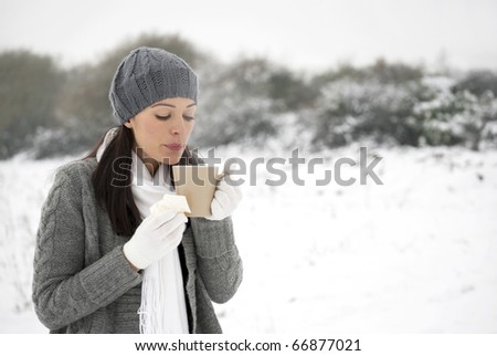 Woman blowing on hot drink holding tissue outside in the snow
