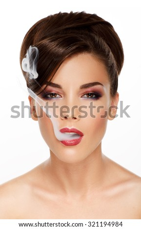 Woman blowing smoke against white background. Studio beauty photo