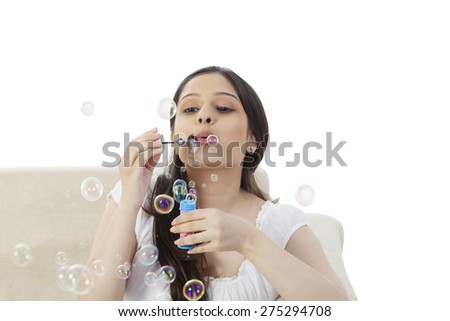 Woman blowing soap bubbles - stock photo