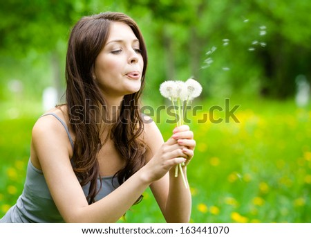 Woman blows dandelions in the park. Concept of nature and rest - stock photo