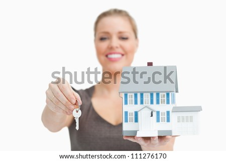 Woman blurred showing a model house and a key against white background