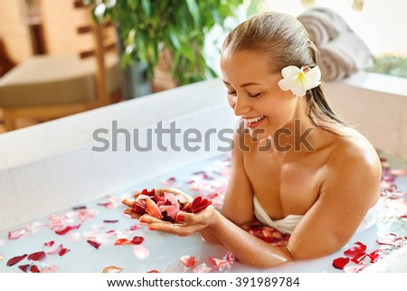 Woman Body Care. Spa Bath With Rose Petals. Close-up Of Sexy Blonde Female In Bikini Taking Flower Bath In Resort Day Spa Centre. Beauty Treatment, Aroma Therapy. Skin Care. Healthy Lifestyle Concept - stock photo