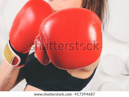 Woman boxer hit straight at the camera, focus on boxing gloves. Woman boxer fist close up