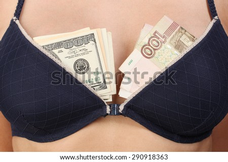 Woman breast in black bra with money (dollars and roubles).