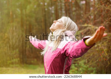 Woman breathes fresh air outdoors in autumn - stock photo