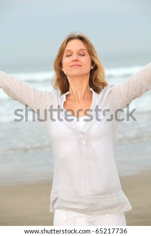 Woman breathing fresh air by the sea - stock photo