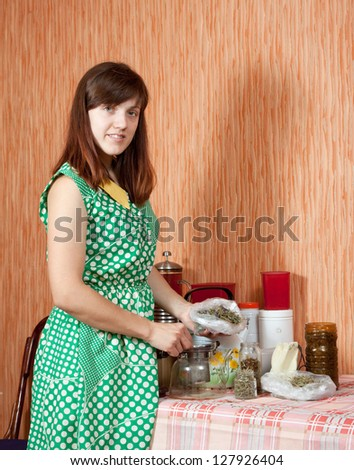 Woman brews herbs in a teapot at home kitchen - stock photo
