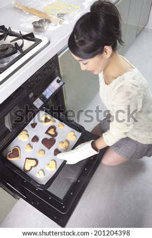Woman bringing cookies up from the oven