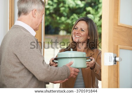Woman Bringing Meal For Elderly Neighbor - stock photo