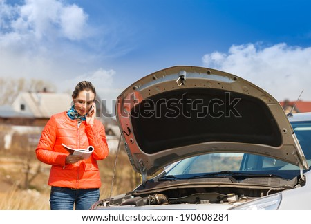 woman  broken car  read  user manual to call for help - stock photo