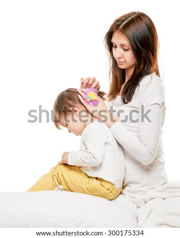 Woman brushing her daughter hair at home on white background