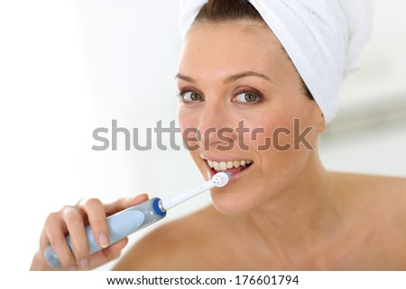 Woman brushing her teeth with electrical toothbrush - stock photo