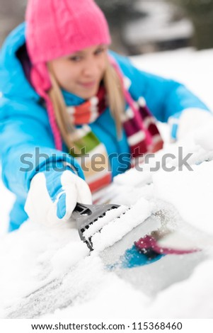 Woman brushing snow from car windscreen winter work scraper wiping