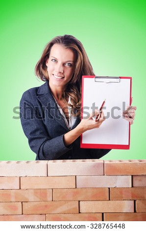 Woman builder and brick wall - stock photo