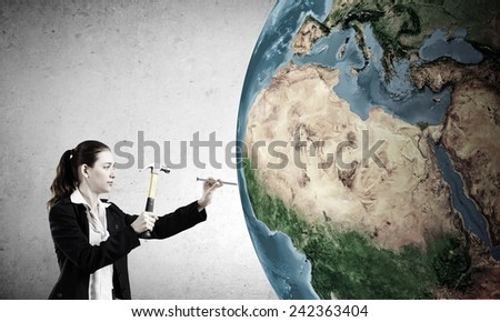 Woman builder hitting nail with hammer in Earth planet. Elements of this image are furnished by NASA - stock photo